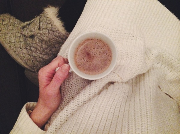 Woman wearing cosy knitwear and slippers, holding a mug of hot chocolate